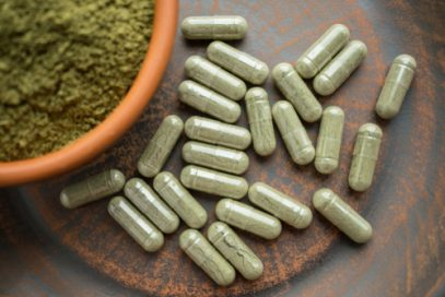 Bowl of Green Kratom and Green UEI Kratom Capsules