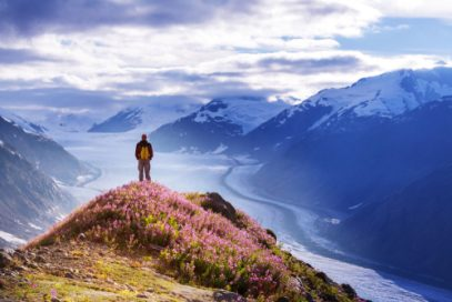 Man on a mountaintop looking at Alaska wilderness Alaska Kratom Legality