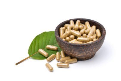 Kratom capsules and leaf.