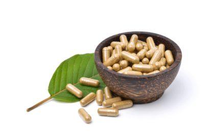 Kratom capsules and leaf.