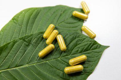 Kratom capsules and leaves